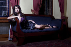 Woman on sofa. Beautiful woman on vintage sofa, luxury interior Royalty Free Stock Image
