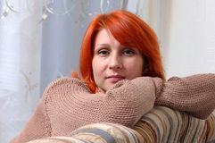 Woman on a sofa. Beautiful woman lying on the sofa royalty free stock image