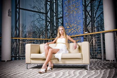 Woman on sofa. Young woman wearing a white dress sitting on a sofa Royalty Free Stock Image
