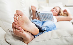 Woman on sofa with book. Barefoot young woman lying on sofa and reading book, shallow depth of field, focus on foot soles Stock Images