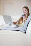 Woman on the sofa booking a flight online Stock Images