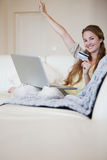 Woman on the sofa celebrating that she won an online auction Royalty Free Stock Images