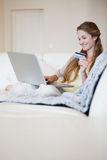 Woman on the sofa doing online shopping Stock Photos