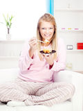 Woman on sofa eating cake at home Royalty Free Stock Photography