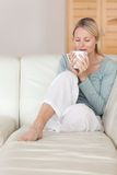 Woman on the sofa enjoying a sip of coffee Royalty Free Stock Photo