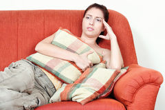 Woman on sofa having headache Royalty Free Stock Images