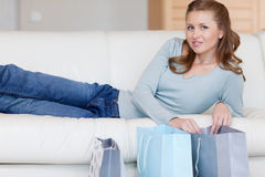 Woman on the sofa with her shopping Stock Images