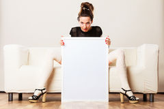 Woman on sofa holding blank presentation board. Stock Image
