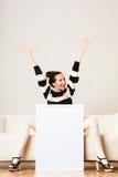 Woman on sofa holding blank presentation board. Royalty Free Stock Photography