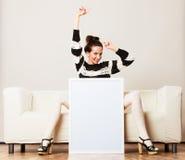 Woman on sofa holding blank presentation board. Royalty Free Stock Photos