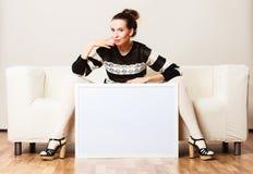 Woman on sofa holding blank presentation board. Stock Photos