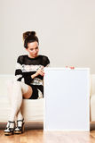 Woman on sofa holding blank presentation board. Stock Images