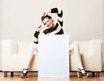 Woman on sofa holding blank presentation board. Stock Photo