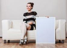 Woman on sofa holding blank presentation board. Stock Image