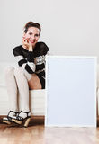 Woman on sofa holding blank presentation board. Royalty Free Stock Image