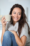 Woman in sofa holding cup Royalty Free Stock Images