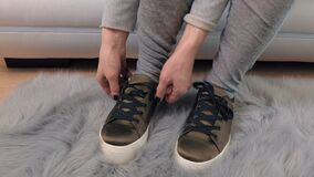 Woman on sofa lace up sneakers. In room stock footage