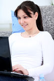 Woman on sofa with laptop computer Stock Photos