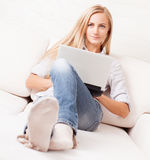 Woman on the sofa with laptop Stock Photos