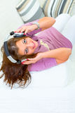 Woman on sofa listening music in headphones Stock Photo