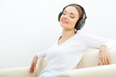 Woman on the sofa listening to music Stock Photos