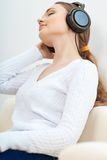 Woman on the sofa listening to music Stock Images