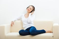 Woman on the sofa listening to music Stock Image