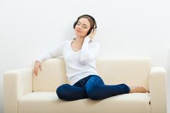 Woman on the sofa listening to music Royalty Free Stock Photos
