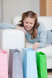 Woman on the sofa looking in her shopping bags Royalty Free Stock Images