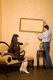 Woman on sofa and man hang up on wall picture Royalty Free Stock Photos