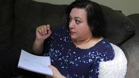 Woman writing with pen. Woman on sofa with a notepad and pen stock video footage