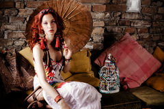 Woman on sofa with parasol. Beautiful red hair woman with japanese parasol sitting on sofa Royalty Free Stock Images