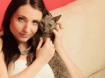 Woman on sofa playing with cat Royalty Free Stock Images
