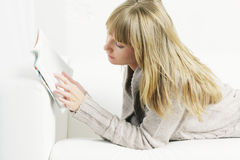 Woman on sofa reading Royalty Free Stock Photography