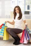 Woman on sofa with shopping bags Stock Images