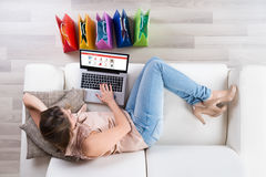 Woman On Sofa Shopping Online With Laptop. Young Woman On Sofa Shopping Online With Laptop Stock Photos