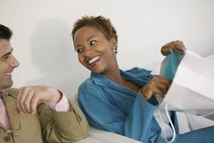 Woman on sofa Showing Man her Purchases. Woman on sofa Showing Man Purchases from Shopping Bag Stock Image