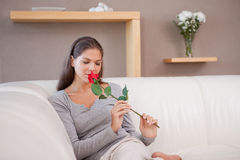 Woman on the sofa smelling on a red rose Stock Photo