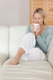 Woman on the sofa taking a sip of coffee Royalty Free Stock Photography