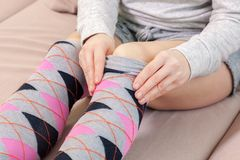 Woman on sofa tidy up over knee socks royalty free stock photography