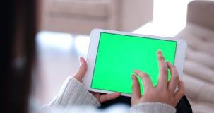 Woman on sofa using tablet computer Stock Photography