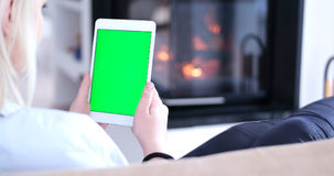 Woman on sofa using tablet computer Stock Images