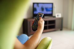 Woman on sofa watching tv changing channel with remote. Over the shoulder view of girl sitting on sofa holding tv remote and surfing programs on television Stock Photography