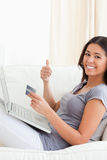 Woman on sofa working with notebook with thumb up Stock Photo