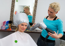 Woman with soft bonnet hair dryer Stock Images