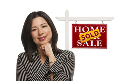 Woman and Sold Home For Sale Real Estate Sign Isolated. Ethnic Woman in Front of Sold Home For Sale Real Estate Sign Isolated on a White Background Royalty Free Stock Photography
