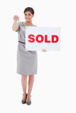 Woman with sold sign handing over key Stock Image