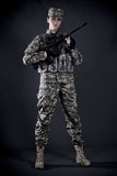 Woman Soldier. Beautiful young woman dressed in grey digital camouflage holding automatic rifle in her hands Stock Photo