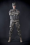 Woman Soldier. Beautiful young woman dressed in grey digital camouflage, hands crossed Royalty Free Stock Images