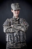 Woman Soldier. Beautiful young woman dressed in grey digital camouflage, hands crossed Royalty Free Stock Photo